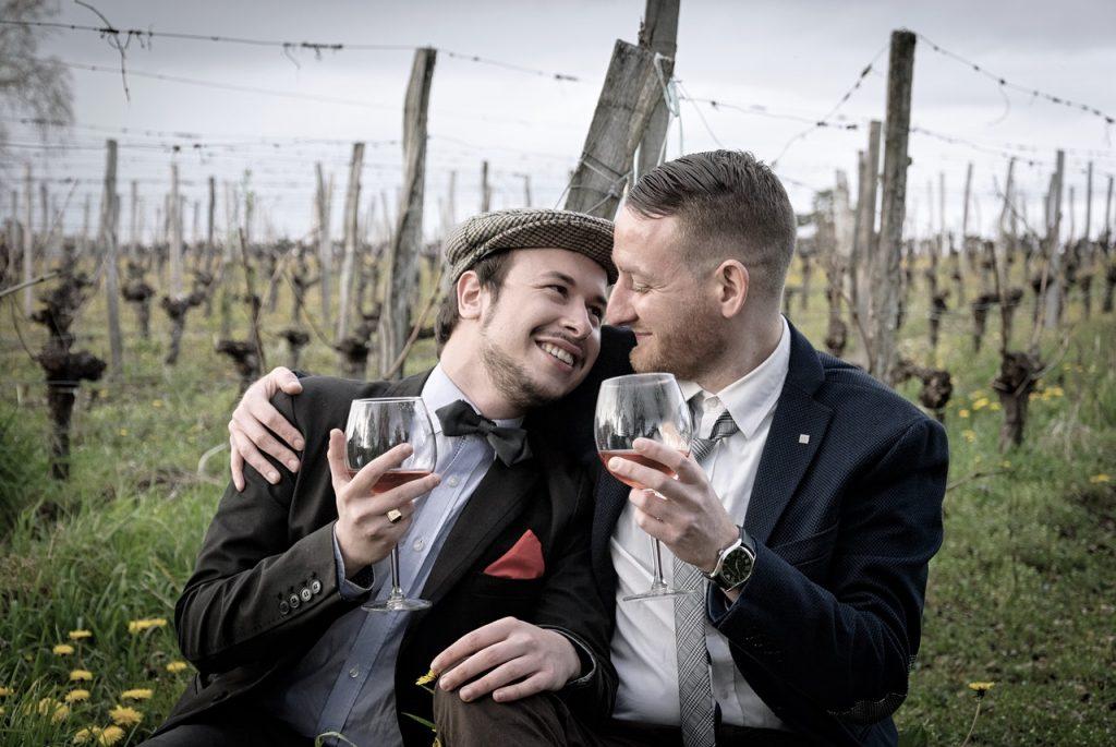 pareja gay, degustando felizmente el vino