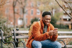 hombre sonriendo mientras escribe o lee un mensaje en su teléfono