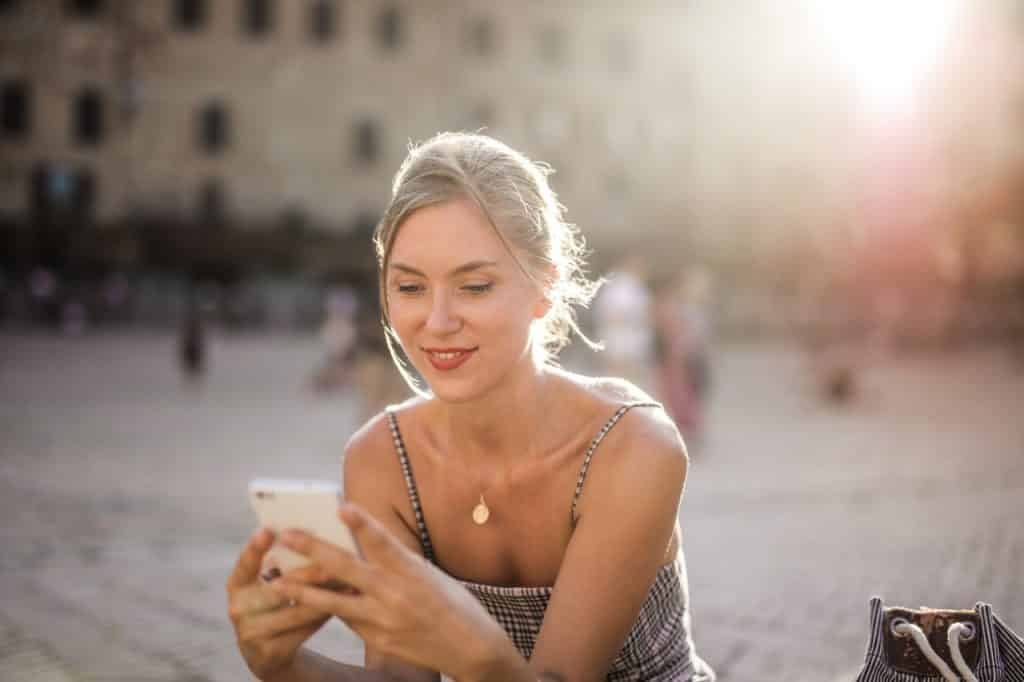 mujer sonriendo mientras escribe o lee un mensaje en su teléfono